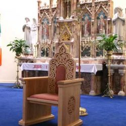 presiders chair with detailed engravings and arms and red upholstered seat reredos right side