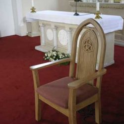 Presiders Chair With Arms and Upholstered seat detailed engraving right side in church
