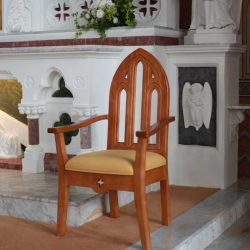 presiders chair right side view with arms yellow upholstered seat and engravings