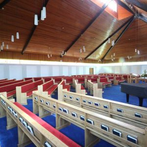 Armagh Free Presbyterian wide view of all benches pews in church bespoke book shelf red upholstered closer