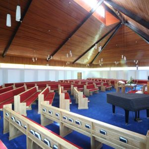Armagh Free Presbyterian wide view of all benches pews in church bespoke book shelf red upholstered closer (2)