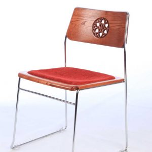 Metal frame stacking chair with bespoke back cut out engravings and red upholstered seat