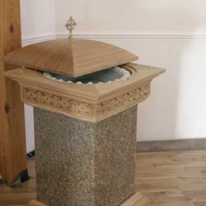 Baptismal font stone effect wooden lid engravings edges crafted excellence