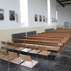 Photo from the back of church with metal frame chairs and wooden benches