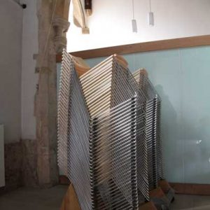 Metal frame chairs stacked 30 high on a trolley making them easy and efficient to move and store