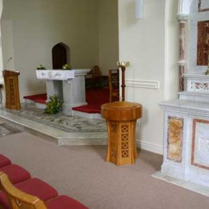 baptismal font at sanctuary of church all wooden cut outs design details bespoke upholstered chairs